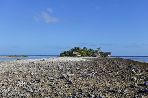 lindblad-south-pacific-thatch-huts.jpg - A Lindblad expedition comes upon locals in thatch huts in the South Pacific.