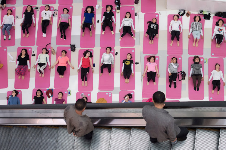 Men look at women attending a yoga session a day ahead of Earth Day, inside a shopping mall in Taiyuan, Shanxi province, China.