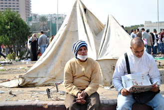 Photo: Men sit on the edge of Tahrir Square, one reading the newspaper about the events that took place the previous day.