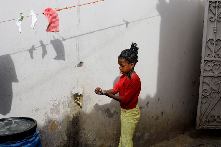 A girl washes her hands at the entrance of her parents' house in Pikine, on the outskirts of Dakar, Senegal, on March 9 2020.