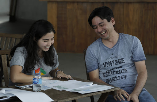 A woman and a man are looking at documents on a table and smiling.