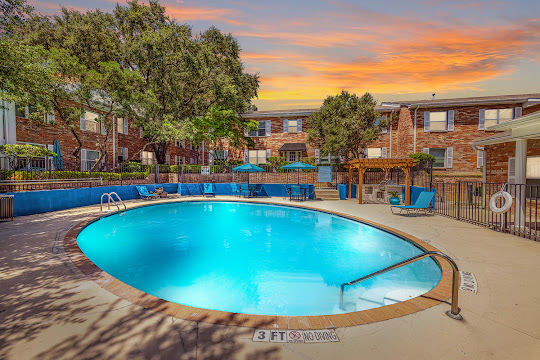 The Colony Uptown's swimming pool with lounge chairs and umbrella covered tables at dusk