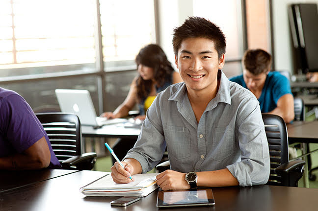smiling male student looking up from his notebook and smiling