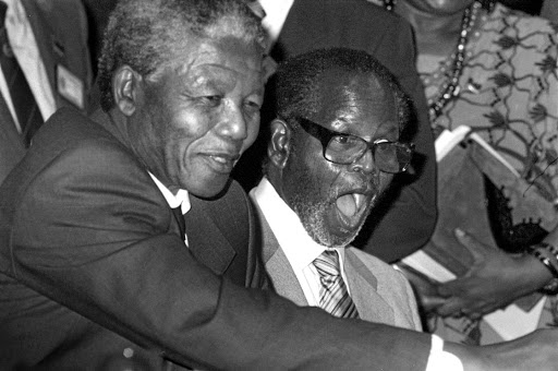 Tambo, with Nelson Mandela next to him, receives a gift