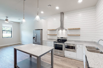 Kitchen with stainless steel appliances, modern hanging light fixtures, wood-inspired flooring, and white cabinets