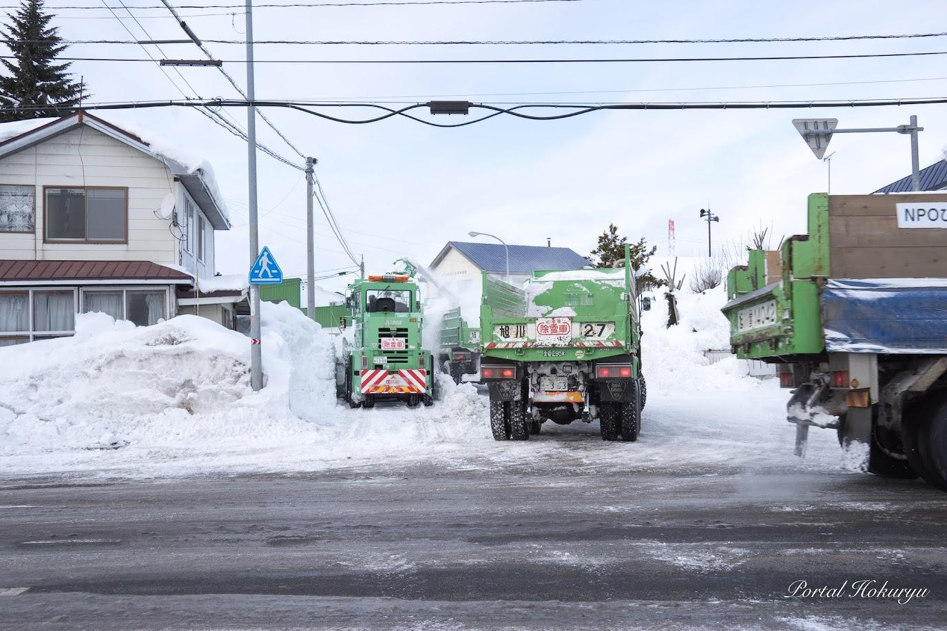 次々と雪を積むダンプ