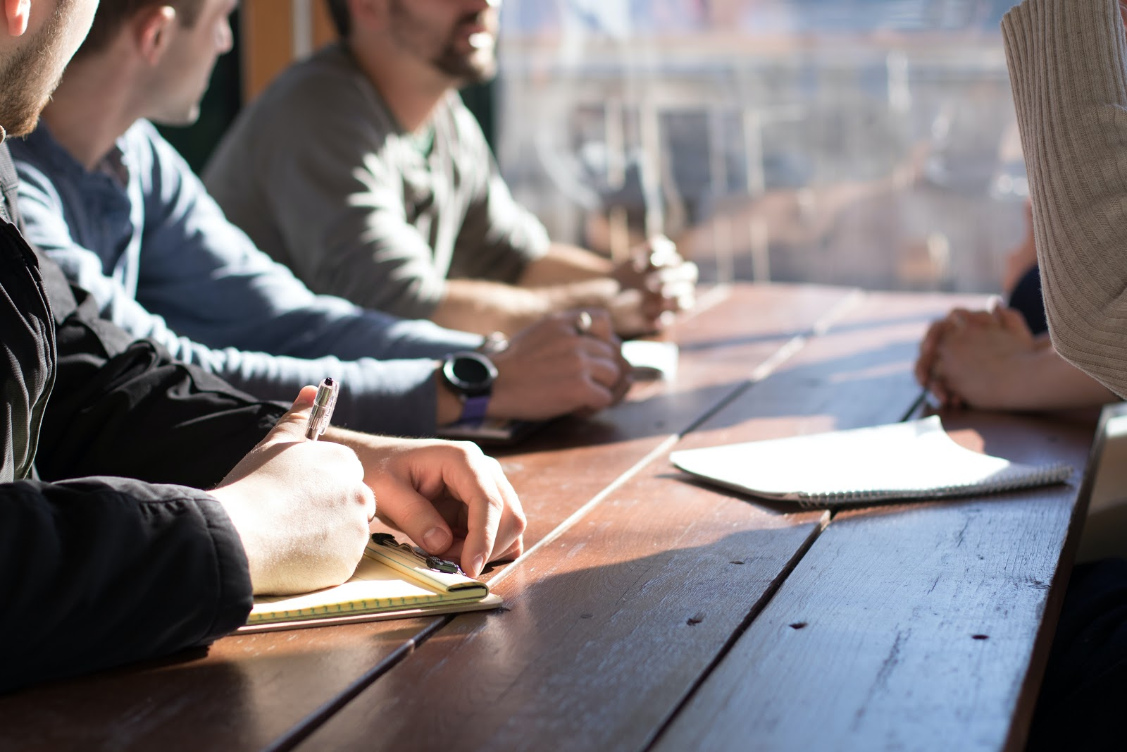 A group of people sitting at a desk in a meeting