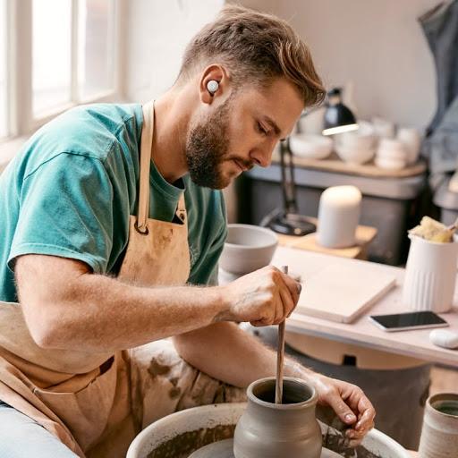 Google Pixel Buds A-Series を付け、長時間駆動バッテリーのおかげでイヤフォンのバッテリー残量を心配することなく陶芸を楽しむ大人の男性。