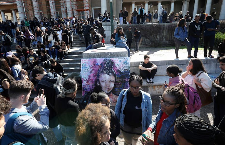 UCT students mill around a painting of the slain 19-year-old.