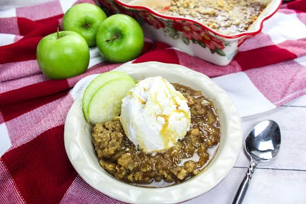 A Bowl Of Apple Crisp With Vanilla Ice Cream.