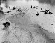 groepjes mensen zittend op rotsgrond bij water