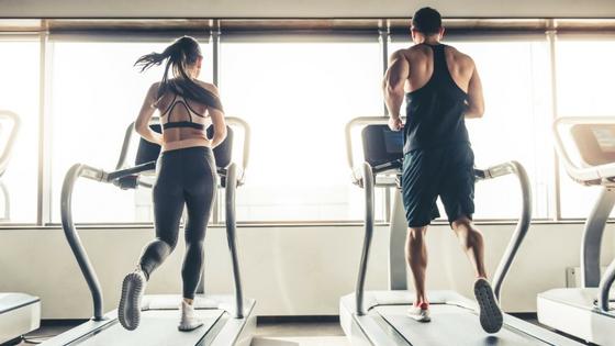 two girls running on treadmills in gym