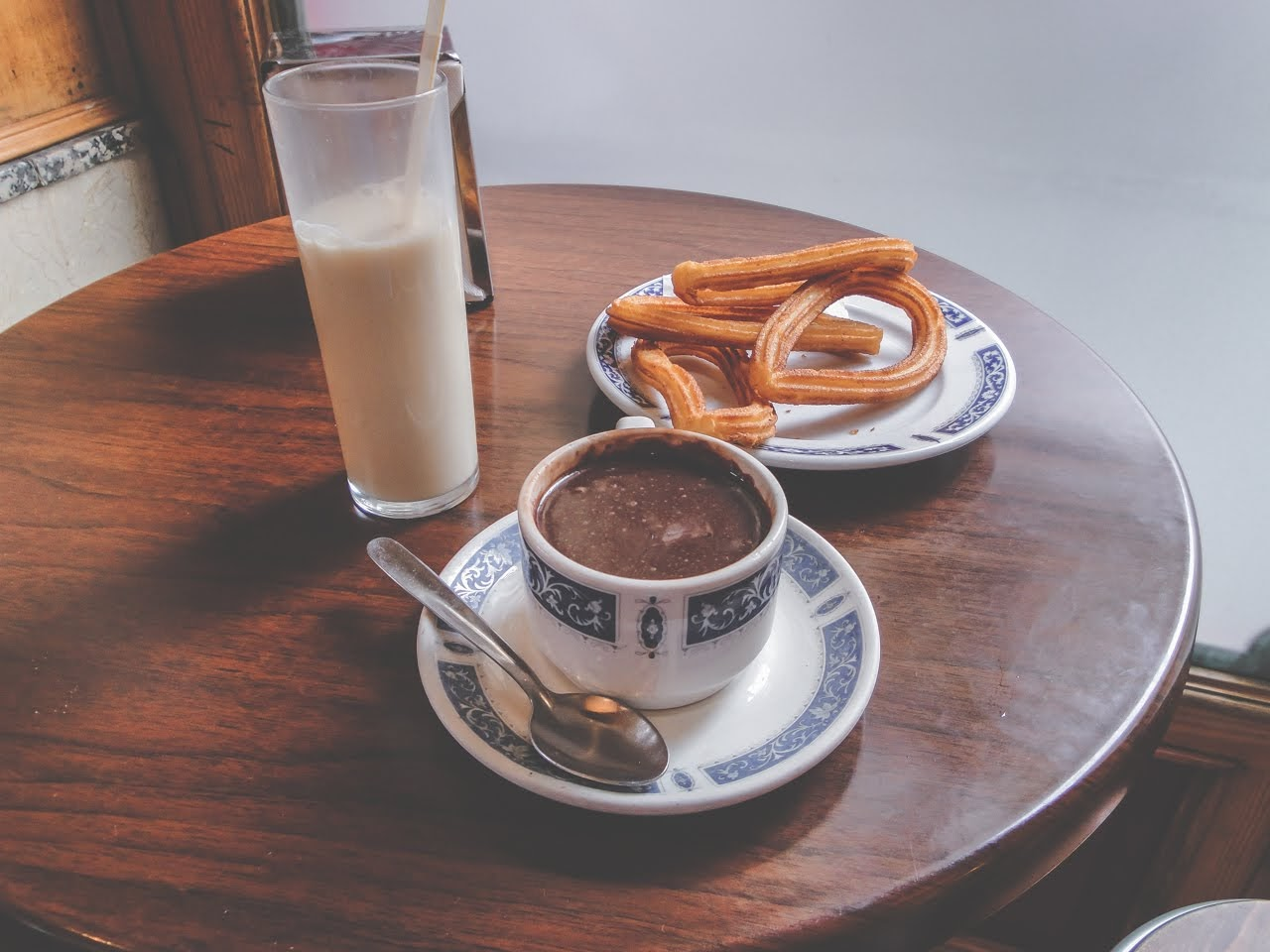 Plat of churros con chocolate and a drink of Horchata on the table ready to eat