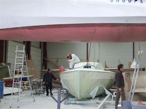 Photo: Le proto de Donatien en réparation au chantier, en arrière plan on s'active pour fermer la boîte