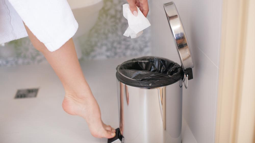 Um pé abrindo um lixo de banheiro.