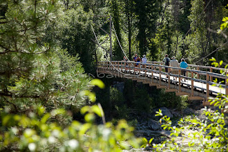 Photo: Group of people crossing walking bridge while on a whitewater raft trip on the Main Salmon River in central Idaho.