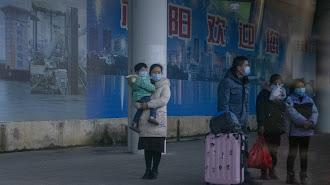 Una familia con una mascarilla en la estación de Nanning.