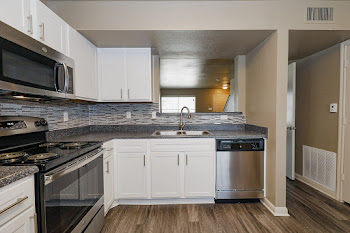B1T Kitchen with White Cabinets, Stainless Steel Appliances, and Dark Countertops