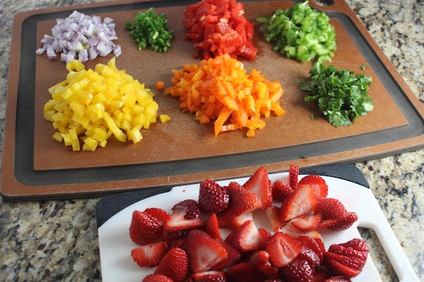 Strawberries, onion, bell peppers, and cilantro sliced on cutting boards.