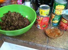 Cook together ground beef and chopped onion.