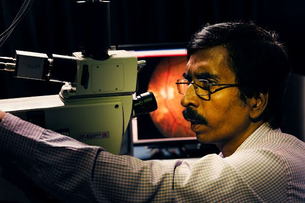 An ophthalmologist looks for damage in a patient's eye scan.