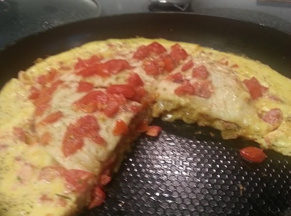Whip eggs with 2-tablespoons water.  Pour over the quesadilla and tomatoes; cover pan.
