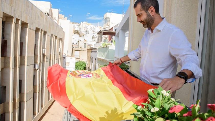 Ramón Fernández-Pacheco colocando una bandera en su balcón el año pasado.