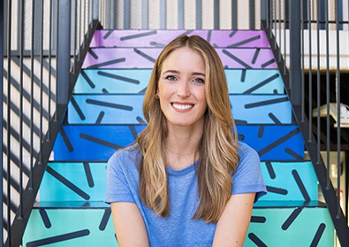 Founder Andrea Barber smiles in front of a colorful staricase