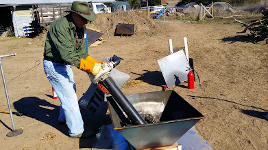 Photo: Michael Wittman empties a pyramid kiln full of biochar with the Stihl leaf blower.