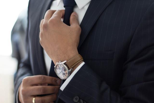 ポーズをとっているスーツ姿の男性自動的に生成された説明
