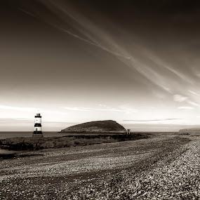 Penmon Beach by Mike Shields - Landscapes Beaches ( clouds, sky, black & white, lighthouse, sea, beach, stones, landscape, rocks )