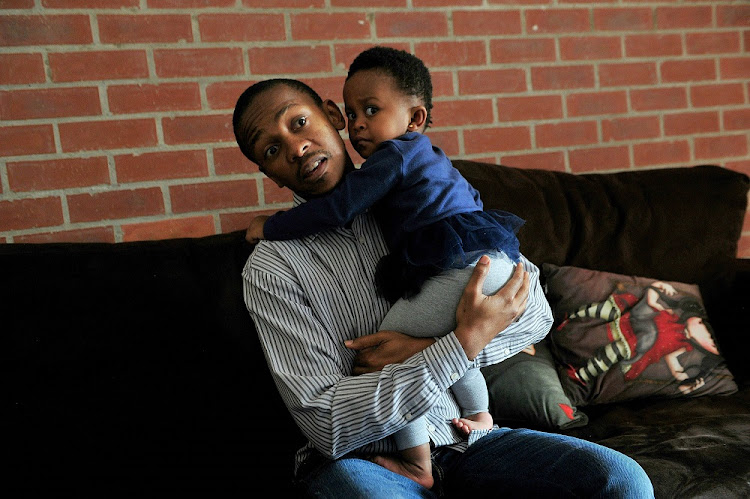 Tshepo Moropa holds baby Phenyo Moropa in Midrand.