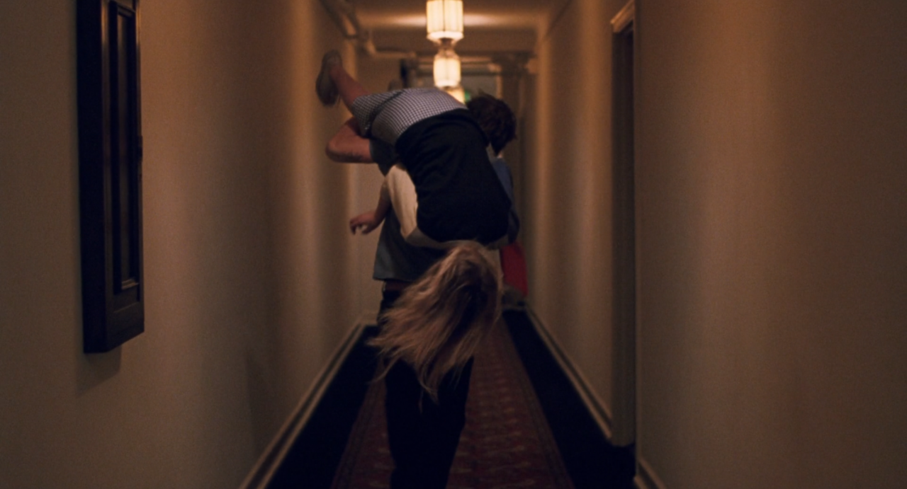 Johnny carrying a laughing Cleo upside down through the Chateau Marmont hallway. The film still catches them from behind as Johnny runs with Cleo on his shoulder. The hallway is subdued but still cosy with warm colours and soft lightning provided by the lamps placed in the middle of the ceiling following the hallway. On the left some kind of dark wooden decoration is present but otherwise the walls are empty. The focus are on the father-daughter pairing as they are placed in the middle of the shot- Focus Features