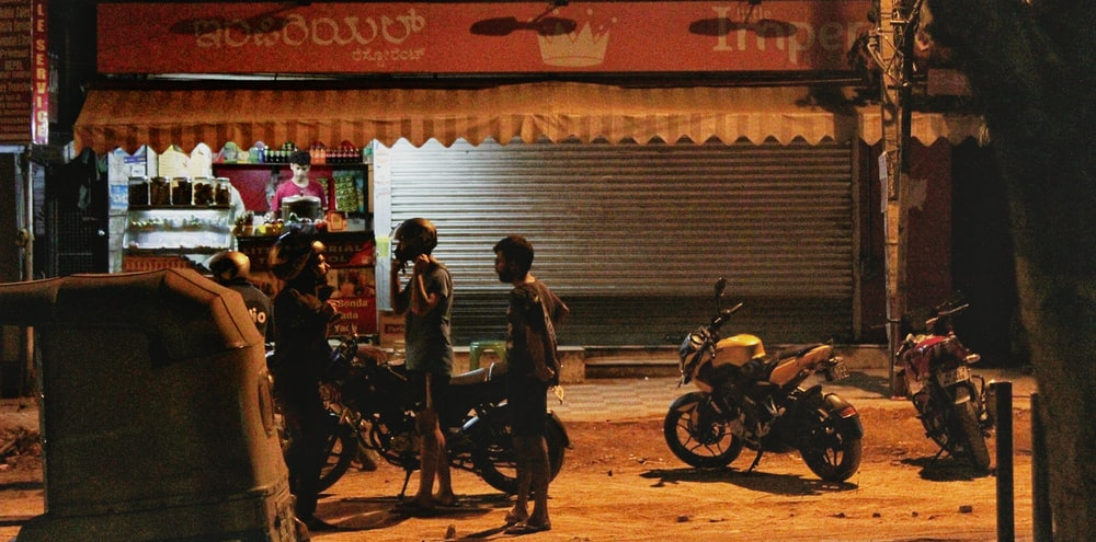 bike riders on a street in front of a tea vendor, late in the night