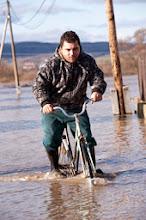 Photo: Ipolytarnóc, 2009. december 26.Rácz Márió kerékpározik gumicsizmában a vízzel borított úttesten a Nógrád megyei Ipolytarnócon, miután az Ipoly kilépett medréből a hajnali órákban; a településen 27 embert kellett kimenekíteni otthonából. Az áradás miatt nyolc ház van veszélyben, amelyből négyet körbevesz a víz, négynek pedig a kertjén folyik keresztül. Az éjszaka kimenekített 27 embert az önkormányzat, illetve a katasztrófavédelem a helyi óvodában helyezte el, ellátásukat biztosítják. Az Észak-magyarországi Környezetvédelmi és Vízügyi Igazgatóság  (Ékövizig) illetékességi területén a készültségben lévő árvízvédelmi szakaszok összes hossza mintegy 215 kilométer, ebből harmadfokú készültség van a Sajón 68 kilométeren, míg másodfokú a riasztás 147 kilométernyi szakaszon.MTI Fotó: Komka Péter