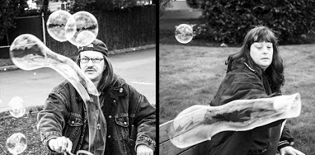 Photo: Joy Bubbles  When you can't smoke in your apartment what do you do? This pair sits at bench on the street and make bubbles for the cars passing by while they toke on their smokes. I was driving by yesterday and couldn't resist stopping for some photos. They are a blast. Their goal is to get you to honk or wave as you pass by and they said they do it everyday when it isn't raining. So the next time you find yourself driving through Newberg give a honk or a wave to the bubble makers. Gotta love their spirit!