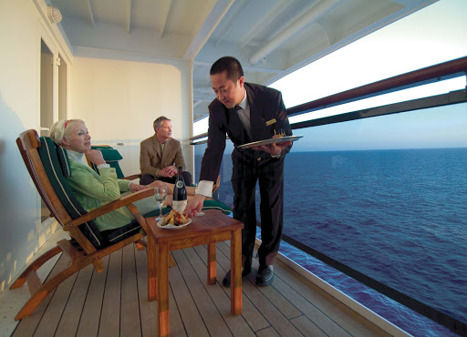 A butler serves guests on their private balcony in a Queens Grill suite (Q5) aboard Queen Mary 2.