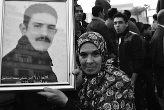 Photo: A woman holds up a picture of a martyr.