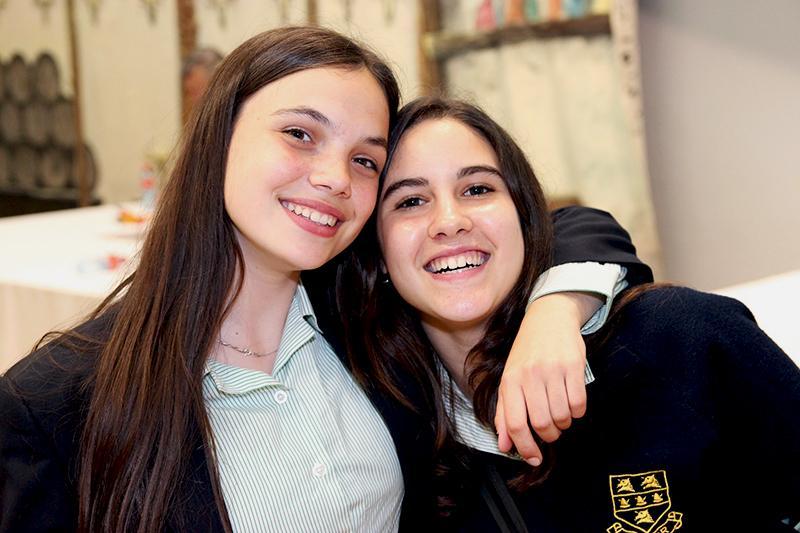 Девочка в школьной форме улыбается и обнимает подругу за плечо