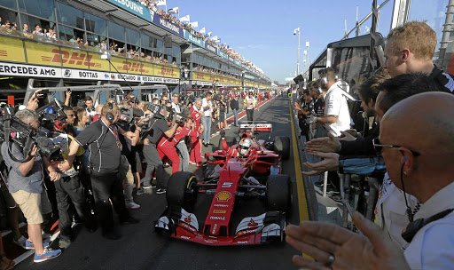Cautious: Ferrari's Sebastian Vettel is welcomed into the pit lane by team members after his victory at the season-opening Australian Grand Prix in March. Picture: REUTERS