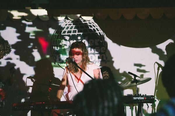 Foto de uma mulher se apresentando, cantando e tocando teclado