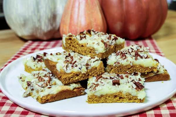 A Stack Of Pumpkin Cream Cheese Bars On A White Plate.