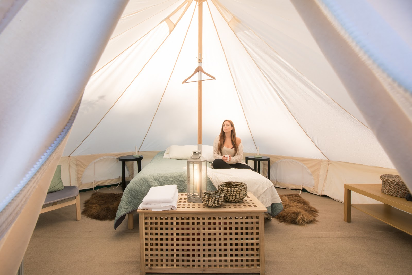 Girl sitting in a glamping tent with a warm drink