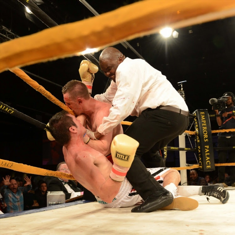 Tony Nyangiwe (referee) breaks the two fighters up during the International Boxing Organisation light heavyweight title match between Johnny Muller (white trunks) and Ryno Liebenberg (red and blue trunks) at Emporors Palace on June 15, 2013 in Johannesburg, South Africa.