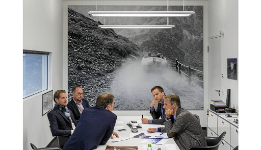 Porsche designers sit in an office with a picture that shows how the brand's DNA was born with a classic 356 on a mountain road in the 1950s