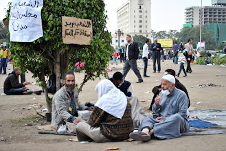 Photo: A group of men sitting in Tahrir Square at midday.