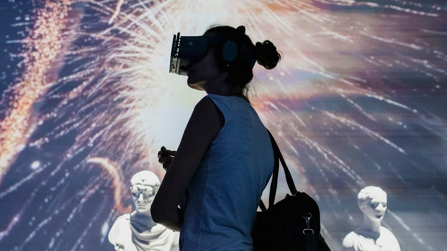 Woman wearing VR headset and standing in front of marble busts and light projection display