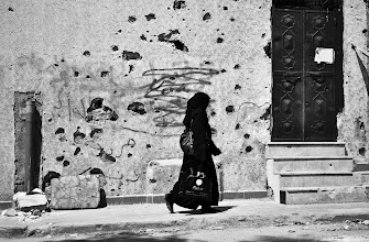 Photo: A woman walks by a battle-torn building in the Khaldiya neighbourhood of Aleppo, Syria. Many areas of the city have seen intense fighting between Syrian rebel fighters and government forces. Aleppo, SYRIA - 30/4/2013. Credit: Ali Mustafa/SIPA Press