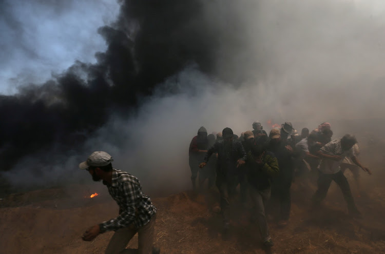 Palestinian demonstrators run for cover during a protest against US embassy move to Jerusalem and ahead of the 70th anniversary of Nakba, at the Israel-Gaza border in the southern Gaza Strip May 14, 2018.
