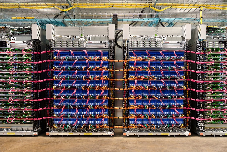 Blue servers stacked high on racks with colorful orange and pink wires